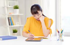 bored asian woman student with tablet pc at home - stock photo