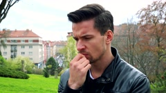 Young handsome serious man stands and thinks about something in park. Stock Footage