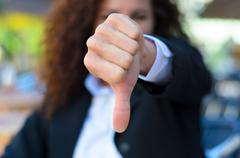 Woman making a thumbs down gesture - stock photo