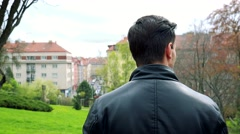 Young handsome man stands and observes landscape in park - detail from behind - stock footage