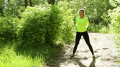 Active young sport woman doing fitness exercises in the park near a forest Stock Footage