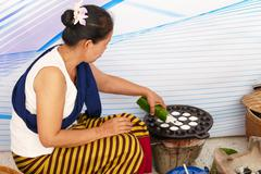 People making sweet and savory grilled coconut rice hotcake - stock photo