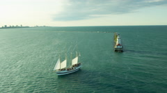 Aerial view of Chicago skyline behind lighthouse and sail boat on Lake Michigan Stock Footage