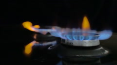 In the kitchen stove ignited the fire in the two burners on a black background Stock Footage
