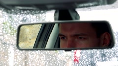 Young handsome man sits in car - detail of face in rear-view mirror - stock footage
