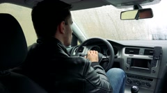 Young handsome man sits in car on place for driver and observes the landscape - stock footage