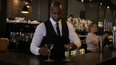 4K Smiling bartender prepares & serves fresh cocktail for a customer Stock Footage