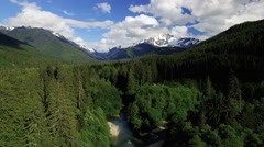 Fly away from Snowy Mountain Mt Baker Nooksack River Aerial Stock Footage
