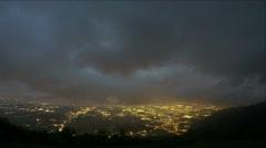 Timelapse of heavy mountain clouds, lights of night city lying below near sea Stock Footage