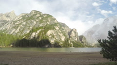 Timelapse of clouds above mountains and lake Pragser Wildsee in Italy, tourism Stock Footage