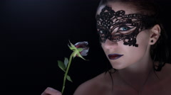 4k shoot of a horror Halloween model - Vampire with mask smelling flower Stock Footage