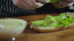 Chef Hands Puts Salad Leaf On A Sandwich Stock Footage