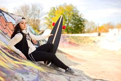 young woman at a skatepark with her board - stock photo