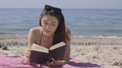 Woman reading book on beach - stock footage