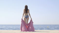 Woman in bikini wrapping towel around Stock Footage