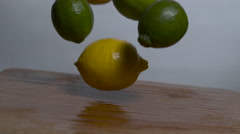 Lemons & Limes falling in slow motion onto a cutting board, barrel roll shot Stock Footage
