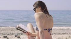 Woman reading book on beach Stock Footage