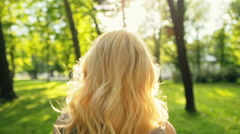 Young woman enjoying spring breeze in the park. The sun is shining. Slow motion Stock Footage