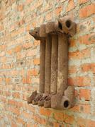 Ruined cast iron radiator for home on a brick wall. - stock photo