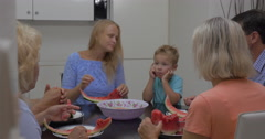 Family with child eating watermelon in the kitchen Stock Footage