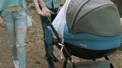 Young family walking with baby in the stroller - stock footage