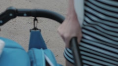 Mother holding the stroller with your hand - stock footage