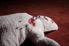 Voodoo Doll with Pins in its Heart Stock Photos