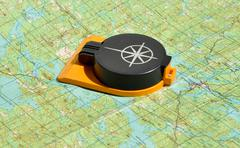 Compass lies on a topographic map. Stock Photos
