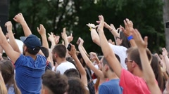 Young spectators fans crowd people cheering sway hands in air jump by a stage - stock footage