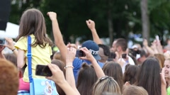Young spectators fans crowd sway hands in air shooting video by a concert stage - stock footage