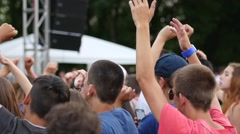 Young spectators fans crowd people cheering sway hands in air jump concert stage - stock footage