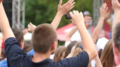 Young spectators fans cheering sway hands in air by a concert stage Stock Footage