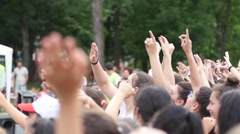 Young spectators fans crowd people cheering sway hands in air by a concert stage - stock footage