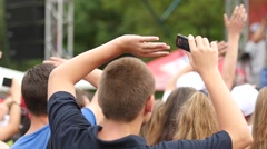 Young spectators fans cheering sway hands in air by a concert stage slow motion Stock Footage