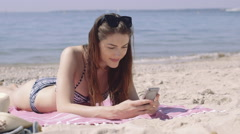 Woman using smart phone on beach vacation Stock Footage