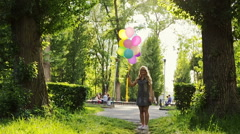 Beautiful young girl having fun at the summer park with colored balloons. Happy Stock Footage