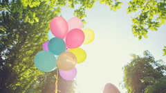 Happy birthday woman against the sky with rainbow-colored air balloons in hands Arkistovideo