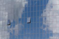 Blue sky and clouds reflected in windows of modern office building - stock photo