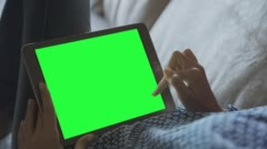 Beautiful girl using tablet pc with pre-keyed green screen laying on sofa 2 - stock footage