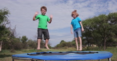 4K Two happy children jumping on trampoline Stock Footage