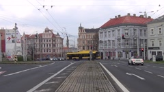 Yellow and blue trolleybus passes frontally through a junction crossroads - stock footage
