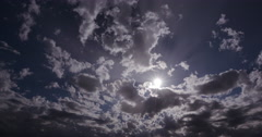 4K Time-lapse of clouds moving in front of the sun Stock Footage
