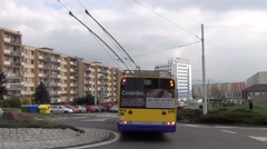 Long yellow and blue trolleybus leaves a roundabout to arrive a stop Stock Footage