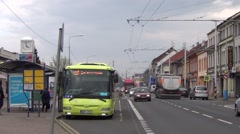 Salad green bus departs from a stop, articulated yellow/blue trolleybus arrives - stock footage
