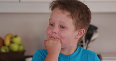 4K Young boy licking chocolate cake mixture off his fingers Stock Footage