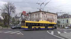 Two yellow/blue trolleybuses and a bus passing a junction near the railway stn. Stock Footage