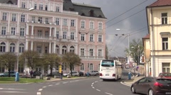 Yellow and blue trolleybus arrives to stop and white bus passes by Stock Footage