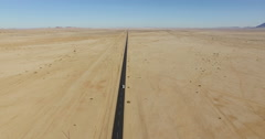 4K Aerial view of car driving on tarred straight road through the Namib desert Stock Footage
