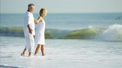 Carefree senior Caucasian couple in white clothing enjoying waves on the beach Stock Footage
