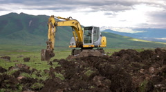 Dolly shot of the excavator digging hole on the mountainous landscape Stock Footage